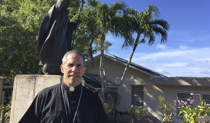 FILE - In this March 3, 2017 file photo, Monsignor Michael Byrnes poses for a photo in front of his residence in Hagatna, Guam. The Vatican officially named Byrnes as Guam's archbishop on Saturday, April 6, 2019, following the definitive sex abuse verdict against his predecessor. (AP Photo/Grace Garces Bordallo, File)