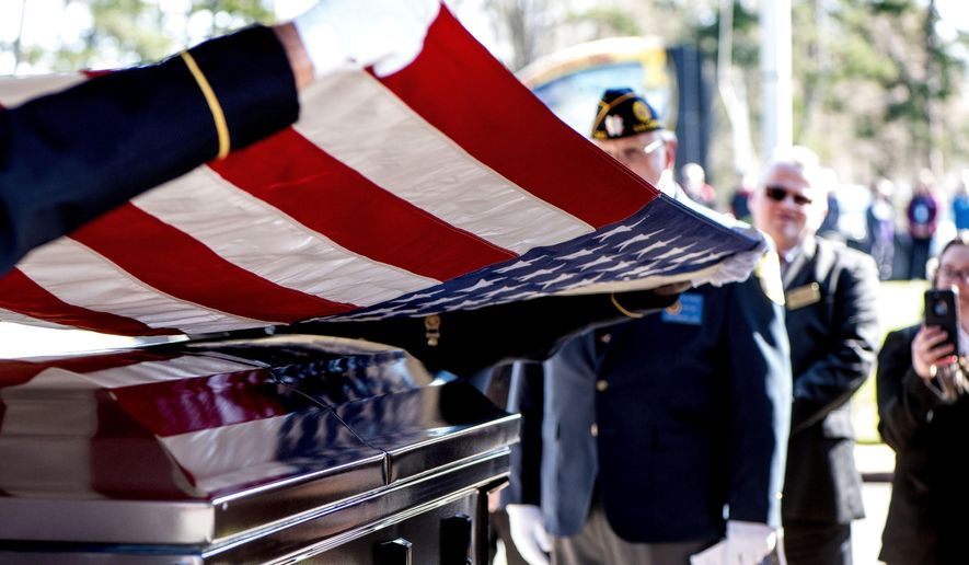 This photo taken April 3, 2019, shows members of the US Army honor guard lifting the American flag off the casket during the burial ceremony at the Salisbury National Cemetery in Salisbury, N.C. US Army medic Phillip Kenneth Drye, a veteran of the Vietnam War, was buried at the Salisbury National Cemetery on Wednesday morning with full military honors. Drye passed away on Dec. 24, 2018, but had no relatives to claim the body and pay for his funeral. (Jon C Lackey/The Salisbury Post via AP)
