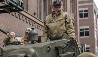 In this Saturday, March 30, 2019, photo, Cpl. Clarence Smoyer settles into a tank as volunteer historical re-enactors roll through lower downtown Denver as part of a ceremony to honor Smoyer, who served with General Maurice Rose of Denver in World War II. (Eric Lubbers/The Colorado Sun via AP)