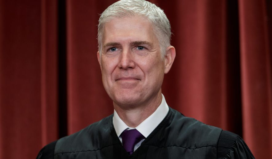 Associate Justice Neil Gorsuch, appointed by President Donald Trump, sits with fellow Supreme Court justices for a group portrait at the Supreme Court Building in Washington, Friday, Nov. 30, 2018. (AP Photo/J. Scott Applewhite)