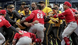 Cincinnati Reds' Yasiel Puig (66) is restrained by Pittsburgh Pirates bench coach Tom Prince, in the middle of a bench clearing brawl during the fourth inning of a baseball game in Pittsburgh, Sunday, April 7, 2019. (AP Photo/Gene J. Puskar) **FILE**