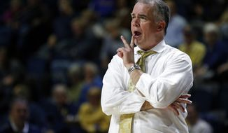 FILE - In this Feb. 28, 2019, file photo, Wofford coach Mike Young yells to his players during the second half of an NCAA college basketball game against Chattanooga in Chattanooga, Tenn. Virginia Tech has hired Young to replace Buzz Williams. The school announced the decision Sunday night, April 7. Young is scheduled to be formally introduced during a news conference Monday morning. (AP Photo/Wade Payne, File)