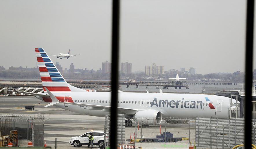 In a March 13, 2019 file photo, an American Airlines Boeing 737 MAX 8 sits at a boarding gate at LaGuardia Airport in New York. American Airlines said Sunday, April 7, 2019, it is extending by over a month its cancellations of about 90 daily flights as the troubled 737 Max plane remains grounded by regulators. The Boeing-made Max jets have been grounded in the U.S. and elsewhere since mid-March, following two deadly crashes in Ethiopia and Indonesia. (AP Photo/Frank Franklin II, File)