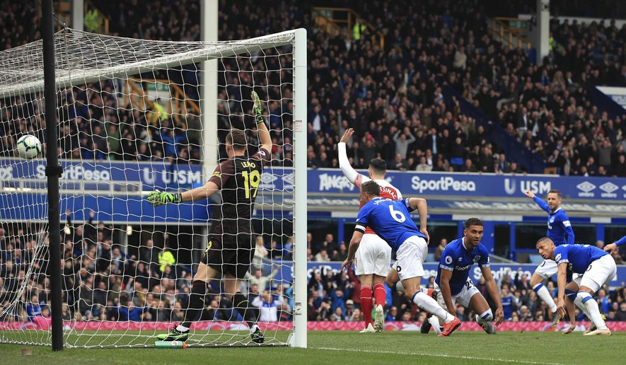 Everton's Phil Jagielka, center, scores his side's first goal of the game as Arsenal players appeal during their English Premier League soccer match at Goodison Park, Liverpool, England, Sunday, April 7, 2019. (Peter Byrne/PA via AP)