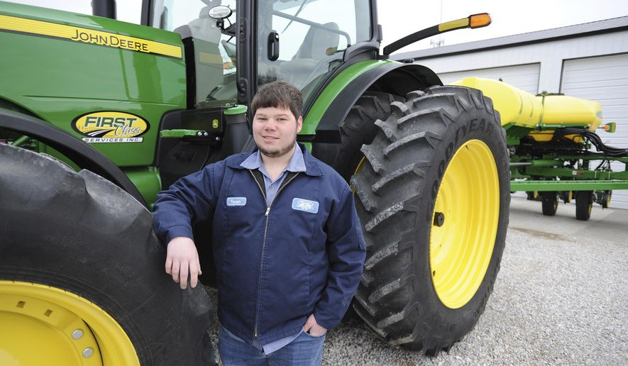 In this March 14, 2019 photo, Tanner Stroup stands by his John Deere 8400 R tractor on his farm in Maceo, Ky. At age 24, Stroup is bringing youth to an otherwise aging profession.  According to the USDA's Census of Agriculture, the average age of a Kentucky farmer is 57.6 years old while the U.S. average is 58.3 years old.  (Alan Warren/The Messenger-Inquirer via AP)