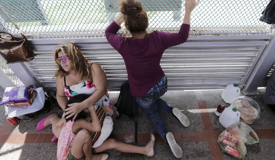 In this June 24, 2018, photo, immigrants from Honduras seeking asylum wait on the Gateway International Bridge, which connects the United States and Mexico, in Matamoros, Mexico. (Associated Press) **FILE**