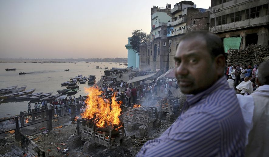 In this March 19, 2019, photo, funeral pyres burn on the banks of river Ganges, in Varanasi, India. According to ancient practice, funeral pyres burn constantly, with the debris and ash shoveled into the river. In the Indian city considered the center of the Hindu universe, Prime Minister Narendra Modi has commissioned a grand promenade connecting the sacred Ganges river with a centuries-old temple dedicated to Lord Shiva, the god of destruction. (AP Photo/Altaf Qadri)