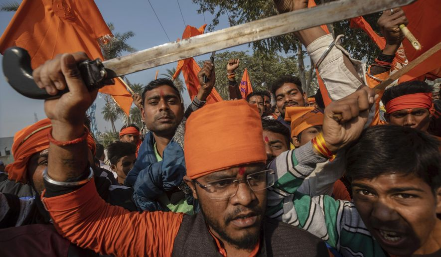 In this Sunday, Nov. 25, 2018 photo, Hindu hardliners, one holding a sword, chant slogans against Muslim communities during a rally demanding a Hindu temple be built on a site in northern India where hardliners in 1992 had attacked and demolished a 16th century mosque in Ayodhya Uttar Pradesh. Riots had left about 2,000 people dead. (AP Photo/Bernat Armangue)