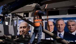 File - In this Wednesday, April 3, 2019 file photo, Israel Electric Corporation employee works next to election campaign billboards showing Israeli Prime Minister and head of the Likud party Benjamin Netanyahu, left, alongside the Blue and White party leaders, from left to right, Moshe Yaalon, Benny Gantz, Yair Lapid, in Tel Aviv. The long-serving Prime Minister Netanyahu is the favorite to win Israel's general election on April 9, but he faces serious corruption charges and a stiff challenge from a former military chief Gantz who has positioned himself as the country's savior. (AP Photo/Oded Balilty, File)
