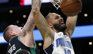 Orlando Magic's Evan Fournier (10) dunks against Boston Celtics' Daniel Theis (27) during the second half of an NBA basketball game in Boston, Sunday, April 7, 2019. (AP Photo/Michael Dwyer)