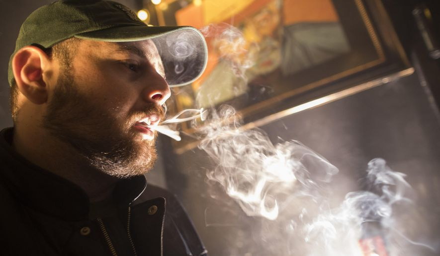 In this Friday, March 29, 2019 photo, a man smokes marijuana at a Spleef NYC canna-cocktail party in New York. As more states make it legal to smoke marijuana, some government officials, researchers and others worry what that might mean for one of the country's biggest public health successes: curbing cigarette smoking. (AP Photo/Mary Altaffer)