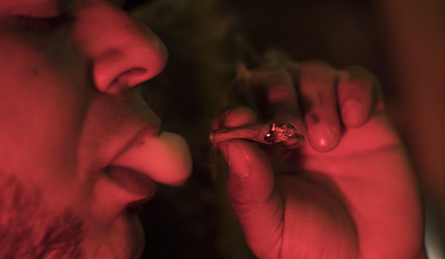 In this Friday, March 29, 2019, file photo, a man smokes a joint at a Spleef NYC canna-cocktail party in New York. As more states make it legal to smoke marijuana, some government officials, researchers and others worry what that might mean for one of the country's biggest public health successes: curbing cigarette smoking. (AP Photo/Mary Altaffer)