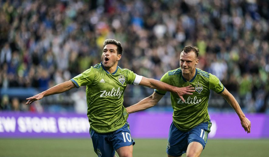Seattle Sounders'  Nicolas Lodeiro, left, celebrates next to Brad Smith after scoring against Real Salt Lake during the first half of an MLS soccer match Saturday, April 6, 2019, in Seattle. (Dean Rutz/The Seattle Times via AP)