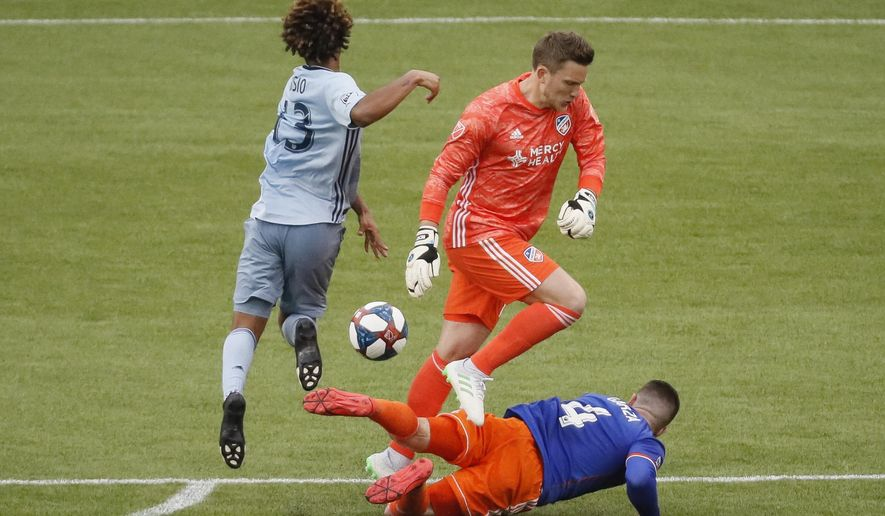 Sporting Kansas City forward Gianluca Busio, left, clears the ball from FC Cincinnati goalkeeper Spencer Richey and defender Greg Garza (4) before scoring on an open goal during the second half of an MLS soccer match Sunday, April 7, 2019, in Cincinnati. (AP Photo/John Minchillo)