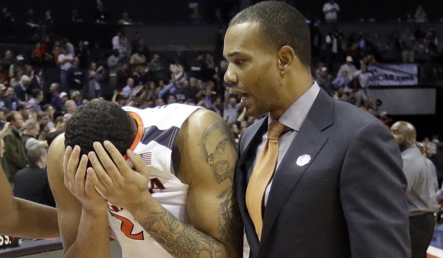 FILE- In this March 16, 2018, file photo, Virginia's Isaiah Wilkins, left, walks off the court after the team's 74-54 loss to UMBC in a first-round game in the NCAA men's college basketball tournament in Charlotte, N.C. Virginia's basketball program, which gave us one of the sport's greatest players in Ralph Sampson and its two biggest upsets, by Division II Chaminade and the world's most famous 16 seed in UMBC, is now on the verge of writing a new chapter _ one that would not be appreciated by nearly as many people were it not for the huge platform Virginia hoops helped create. (AP Photo/Gerry Broome, File) **FILE**