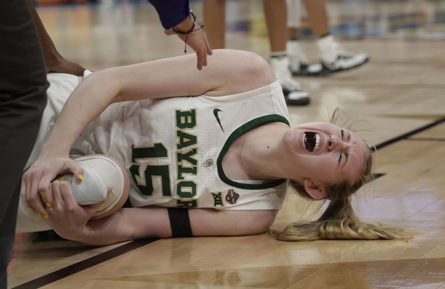 Baylor forward Lauren Cox yells as she holds her left knee, during the second half against Notre Dame in the Final Four championship game of the NCAA women's college basketball tournament Sunday, April 7, 2019, in Tampa, Fla. (AP Photo/John Raoux)