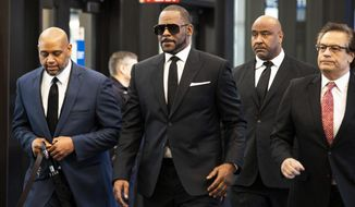 FILE - In this March 22, 2019 file photo, R. Kelly walks with attorneys and supporters into the Leighton Criminal Courthouse in Chicago. Kelly gave a 28-second performance and spent about half an hour more hobnobbing with fans who paid $50 to $100 to see him at a club in the Illinois capital of Springfield. The R&B singer posted a video on his Instagram page hours before the early Sunday, April 7 performance at the Dirty South Lounge. In the video, Kelly calls on the media to take it easy on him, saying he needs to perform in order to make money amid the sexual abuse case he faces.  (Ashlee Rezin/Chicago Sun-Times via AP, File)