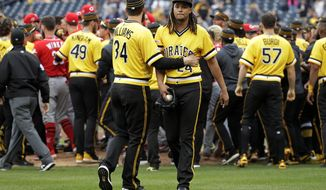 Pittsburgh Pirates starting pitcher Chris Archer (24) walks away from a bench clearing brawl with fellow pitcher Trevor Williams (34) during the fourth inning of a baseball game in Pittsburgh, Sunday, April 7, 2019. A wild pitch by Archer during an at-bat by Reds' Derek Dietrich started the fight. (AP Photo/Gene J. Puskar)
