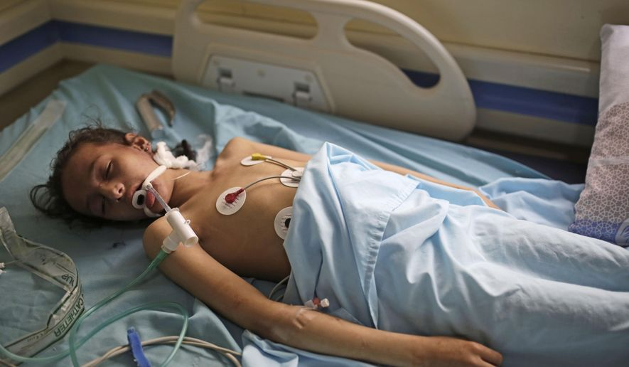 A Yemeni girl who was injured in an explosion lies in a bed at a hospital in Sanaa, Yemen, Sunday, April 7, 2019. Yemeni medical officials say a big explosion at a warehouse in the capital killed at least seven children in nearby schools and wounded over 50 people, including schoolchildren. The rebels say an airstrike by the Saudi-led coalition targeted the warehouse and damaged nearby schools. The Houthi rebels, who have controlled the capital since 2014, sealed off the area. (AP Photo/Hani Mohammed)