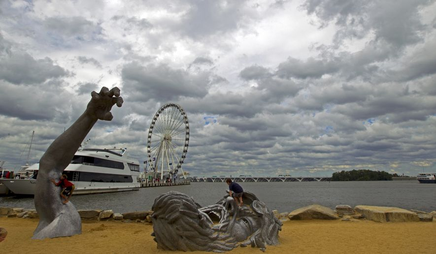 "In this Sept. 3, 2016, file photo, children play on J. Seward Johnson's sculpture, ""The Awakening,"" along the Potomac River waterfront at National Harbor, Md. Federal prosecutors say a man inspired by the Islamic State group stole a U-Haul truck with plans to drive it into a crowd at National Harbor, a convention and tourist destination just outside the nation's capital. (AP Photo/Jose Luis Magana, File)"
