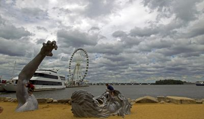 """In this Sept. 3, 2016, file photo, children play on J. Seward Johnson's sculpture, """"The Awakening,"""" along the Potomac River waterfront at National Harbor, Md. Federal prosecutors say a man inspired by the Islamic State group stole a U-Haul truck with plans to drive it into a crowd at National Harbor, a convention and tourist destination just outside the nation's capital. (AP Photo/Jose Luis Magana, File)"""