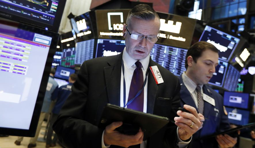 In this April 2, 2019, file photo traders Neal Catania, left, and Benjamin Tuchman work on the floor of the New York Stock Exchange. (AP Photo/Richard Drew, File)