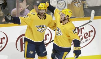 Nashville Predators center Colton Sissons (10) celebrates with Austin Watson (51) after Sissons scored against the Chicago Blackhawks during the third period of an NHL hockey game Saturday, April 6, 2019, in Nashville, Tenn. The Predators won 5-2. The win gave the Predators first place in the Central Division for the Stanley Cup playoffs. (AP Photo/Mark Humphrey)