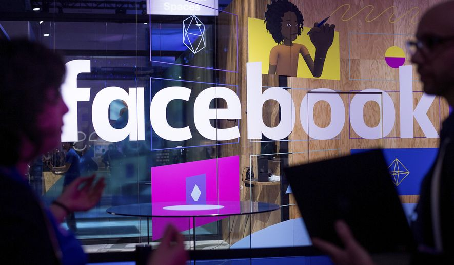 In this April 18, 2017, file photo, conference workers speak in front of a demo booth at Facebook's annual F8 developer conference, in San Jose, Calif. The U.K. for the first time on Monday, April 8, 2019, proposed direct regulation of social media companies, with senior executives potentially facing fines if they fail to block damaging content such as terrorist propaganda or images of child abuse. (AP Photo/Noah Berger, File)