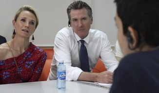 California Gov. Gavin Newsom, and his wife, Jennifer Siebel Newsom hear the stories of three migrants who fled El Salvador due to violence and poverty and tried to reach the United States with last year's migrant caravans, during his visit to La Chacra Immigration Center in San Salvador, El Salvador, Monday, April 8, 2019. (AP Photo/Salvador Melendez)