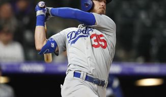 Los Angeles Dodgers' Cody Bellinger follows the flight of his solo home run off Colorado Rockies relief pitcher Bryan Shaw in the eighth inning of a baseball game Sunday, April 7, 2019, in Denver. (AP Photo/David Zalubowski)