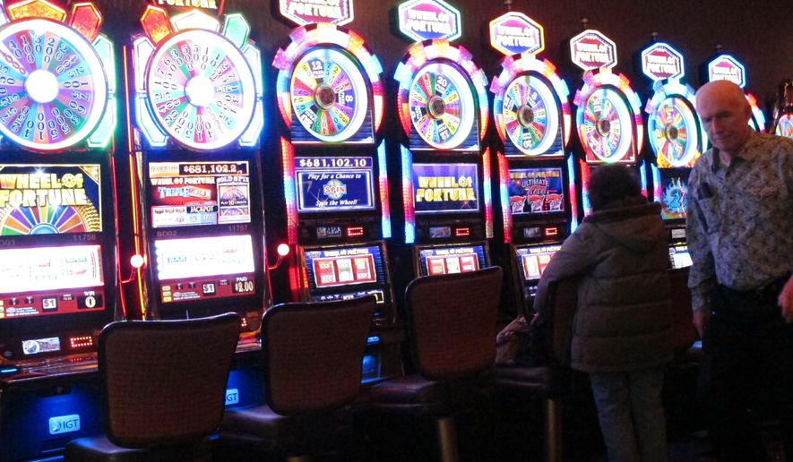 This Feb. 22, 2019, photo shows gamblers playing slot machines at the Golden Nugget casino in Atlantic City, N.J. Figures released on Monday, April 8, show that gross operating profits for Atlantic City casinos declined by more than 15 percent in 2018 as two shuttered casinos reopened, adding to the competition for existing casinos. (AP Photo/Wayne Parry)