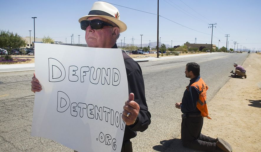 FILE - In this May 20, 2015 file photo, Paul Murray of Santa Barbara, Calif., demonstrates with others outside Adelanto Detention Facility in Adelanto, Calif. For nearly eight years, Adelanto has joined with a private prison company and federal officials to run California's largest immigration detention facility. Now, the city of Adelanto is backing out of its contract to run the 1,900 bed facility amid complaints of shoddy conditions and inadequate medical care. But ending the deal won't necessarily shutter the center and rather, could pave the way for its expansion. (James Quigg/The Victor Valley Daily Press via AP, File)