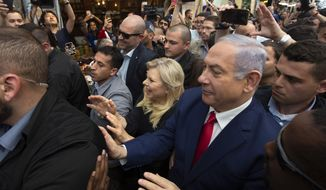 Israeli Prime Minister Benjamin Netanyahu, right, escorted by bodyguards walks with his wife Sara Netanyahu during a visit to the market on the eve of Israel's general elections in Jerusalem, Monday, April 8, 2019. (AP Photo/Sebastian Scheiner)