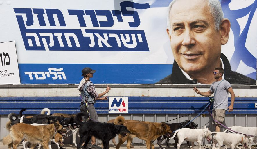 "Dog walkers argue as they pass by an election campaign billboard shows Israeli Prime Minister Benjamin Netanyahu in Tel Aviv, Israel, Monday, April 8, 2019. Israel's election on Tuesday boils down to a referendum on Prime Minister Benjamin Netanyahu, who has dominated the country's politics for the better part of three decades. The Hebrew writing say ""Strong Likud, Strong Israel. (AP Photo/Ariel Schalit)"