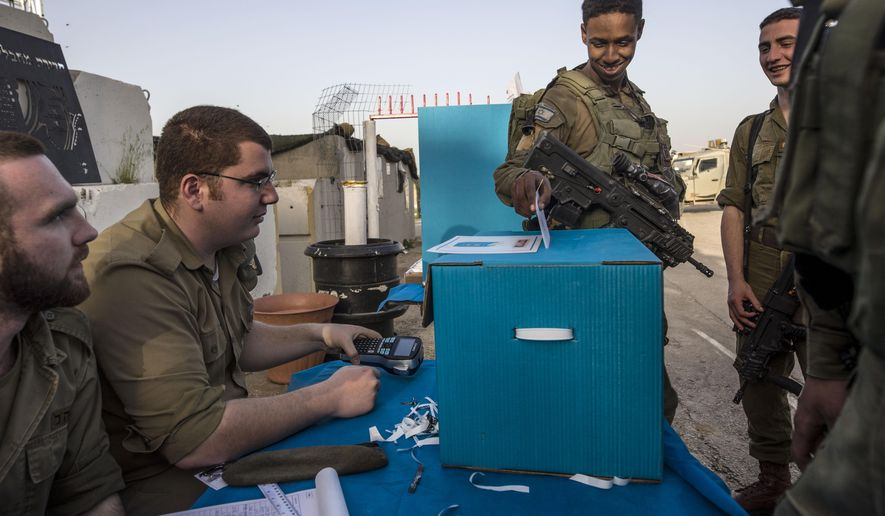 Israeli soldiers cast their ballots oat a mobile voting booth, two days before polling stations open in the rest of Israel, at a military post on the northern Israel and Gaza border, Sunday, April 7, 2019. (AP Photo/Tsafrir Abayov)