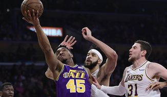 Utah Jazz guard Donovan Mitchell, left, shoots as Los Angeles Lakers center JaVale McGee, center, and forward Mike Muscala defend during the first half of an NBA basketball game Sunday, April 7, 2019, in Los Angeles. (AP Photo/Mark J. Terrill)