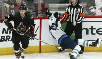 Arizona Coyotes defenseman Kevin Connauton (44) sends Winnipeg Jets center Jack Roslovic (28) into referee Chris Lee during the third period of an NHL hockey game Saturday, April 6, 2019, in Glendale, Ariz. The Jets defeated the Coyotes 4-2. (AP Photo/Ross D. Franklin)