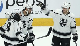 Los Angeles Kings defenseman Drew Doughty (8) celebrates his empty-net goal against the Arizona Coyotes with Kings center Anze Kopitar, middle, and right wing Dustin Brown (23) during the third period of an NHL hockey game, Tuesday, April 2, 2019, in Glendale, Ariz. The Kings defeated the Coyotes 3-1. (AP Photo/Ross D. Franklin)