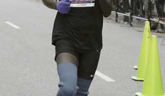 FILE - In this Aug. 19, 2018, photo, Marko Cheseto, a college All-American who lost both feet to frostbite after being stranded outside in an Alaskan blizzard in 2011, competes in the Skinny Raven Half Marathon during the Anchorage RunFest in Anchorage, Alaska. After making his marathon debut in New York in 2018, Cheseto will run in the Boston Marathon on April 15, 2019, with the goal of competing in the race's new Para Athlete division in 2020. (Bill Roth/Anchorage Daily News via AP, File)/Anchorage Daily News via AP, File)