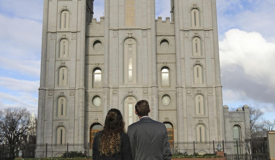 A couple looks at the Salt Lake City temple during the The Church of Jesus Christ of Latter-day Saints' two-day conference Saturday, April 6, 2019, in Salt Lake City. Church members are preparing for more changes as they gather in Utah for a twice-yearly conference to hear from the faith's top leaders. (AP Photo/Rick Bowmer)