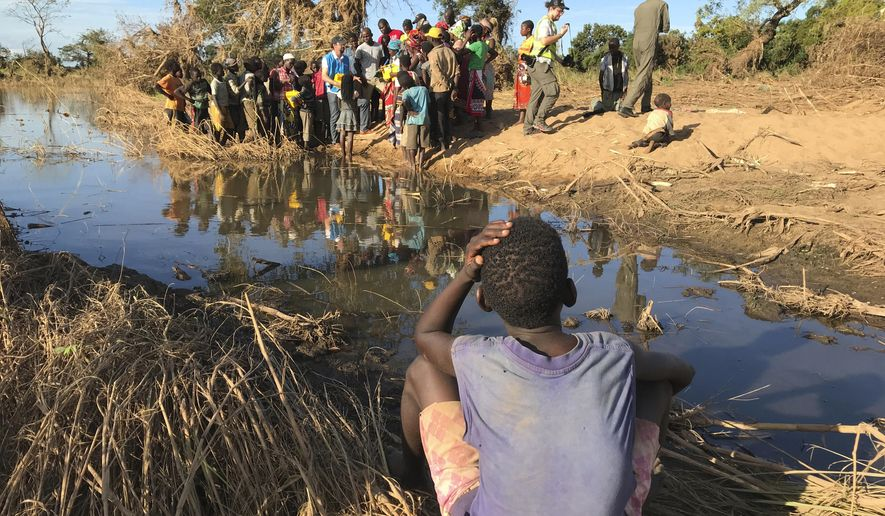 In this photo taken Saturday, April 6, 2019 a boy watches a demonstration of water filters in the remote village of Bopira, Mozambique. Crops across the region were destroyed by Cyclone Idai just before the harvest, raising concerns about hunger in the months ahead. (AP Photo/Cara Anna)