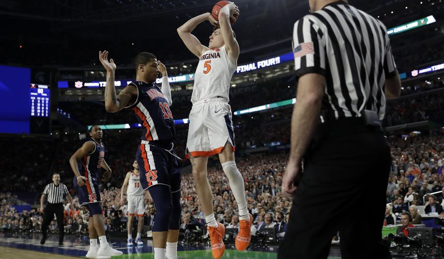 FILE - In this April 6, 2019, file photo, Virginia's Kyle Guy (5) takes a shot as Auburn's Samir Doughty (10) was called for a foul during the second half in the semifinals of the Final Four NCAA college basketball tournament, in Minneapolis. Guy sank all three free throws and Virginia defeated Auburn 63-62. (AP Photo/David J. Phillip, File)