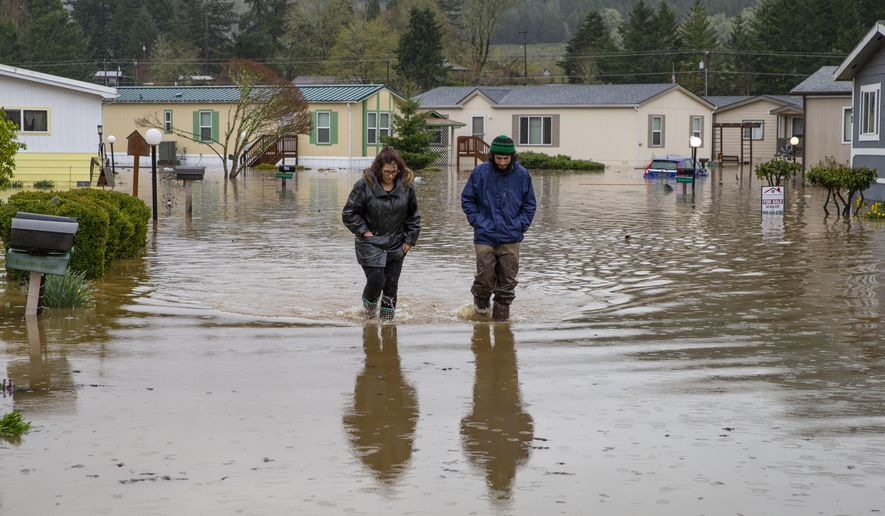 Shannon Archuleta, left, and her son Jett Archuleta wade through a flooded street in the Riverstone Mobile Home Park in Cottage Grove, Ore. Monday April, 8, 2019 to check on a family member after flood waters rose overnight. [Chris Pietsch/The Register-Guard via AP)