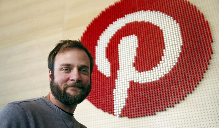 In this Oct. 11, 2018, file photo, Evan Sharp, Pinterest co-founder and chief product officer, poses for a photo beside a wall of pegs symbolizing the company logo at Pinterest headquarters in San Francisco. Pinterest plans to raise up to approximately $1.47 billion in its initial public offering. (AP Photo/Ben Margot, File)