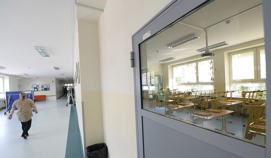 A woman walks through the corridor near an empty classroom at the Primary School number 68 in Warsaw, Poland, on Monday, April 8, 2019. Majority of Poland's school and kindergarten teachers went on strike after talks about their payment with the government failed. (AP Photo/Czarek Sokolowski)