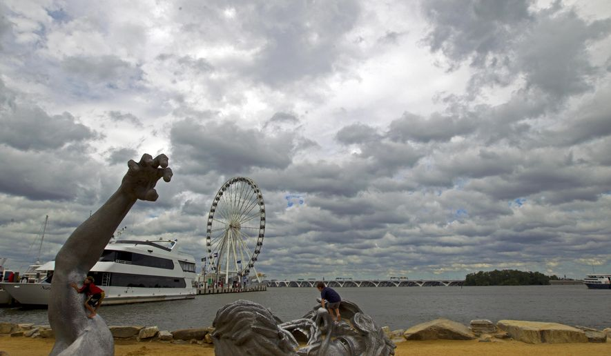 "FILE - In this Sept. 3, 2016, file photo, children play on J. Seward Johnson's sculpture, ""The Awakening,"" along the Potomac River waterfront at National Harbor, Md. Federal prosecutors say a man inspired by the Islamic State group stole a U-Haul truck with plans to drive it into a crowd at National Harbor, a convention and tourist destination just outside the nation's capital. (AP Photo/Jose Luis Magana, File)"