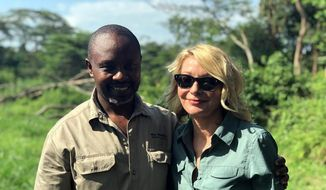 Image released by Wild Frontiers tour company on Monday April 8, 2019, shows American tourist Kim Endicott, right, and field guide Jean-Paul Mirenge a day after they were rescued following a kidnap by unknown gunmen in Uganda's Queen Elizabeth National Park. Ugandan police said on Sunday they had rescued Endicott, an American tourist, and her guide, Mirenge, who had been kidnapped by gunmen in a national park. (Wild Frontiers via AP)