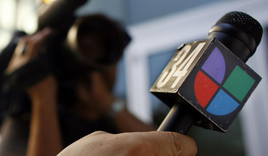 In this June 14, 2006, photo a journalist holds a microphone bearing the Univision logo in Los Angeles. (Associated Press) **FILE**