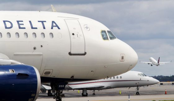 In this Aug. 8, 2017, photo, a Delta Air Lines jet waits on the tarmac at LaGuardia Airport in New York. Delta tops an annual study that ranks U.S. airlines by on-time arrivals, complaint rates, and other statistical measurements. Researchers who crunch the numbers say that U.S. airlines are getting better as a whole. (AP Photo/Mary Altaffer, File)