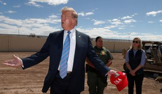 President Donald Trump visits a new section of the border wall with Mexico in Calexico, Calif., Friday April 5, 2019. Gloria Chavez with the U.S. Border Patrol, center, and Homeland Security Secretary Kirstjen Nielsen listen. (AP Photo/Jacquelyn Martin)